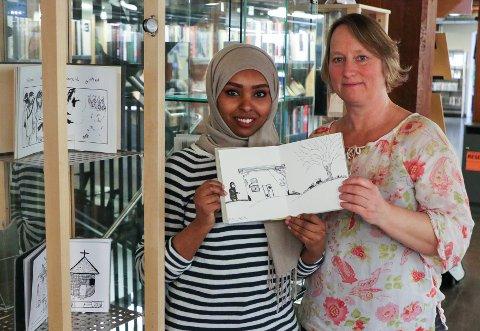 BOKPROSJEKT: Billedkunstner Sophie Rodin (til høyre) viser utstillingen «Min bok, Min stemme» på Moss bibliotek. Det er bøker med tegninger laget av asylsøkere. Aicha Halloita har tegnet seg selv foran huset hun bodde i i Saudi-Arabia.