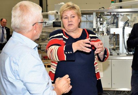 LÆRTE MYE: Statsminister Erna Solberg besøkte Tronrud Engineering på Eggemoen. Her får hun en innføring av prosjektleder Geir Atle Ekås ved en av maskinene som produserer flasker. – Et viktig kunnskap, mener statsministeren.