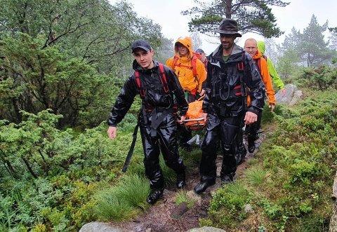 REDNINGSOPPDRAG: Ti av dei lokale folkehjelpsmannskapa bar ein uheldig turågar ned frå fjellet på Reinarknuten-stien.