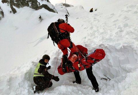 Her blir den skredtatte mannen løftet ut fra snømassene. Foto: Luftambulansen Evenes