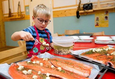 Amund Stendahl (4) er vant til å lage og liker mye forskjellig mat. Her legger han fetaost og krydder på ferske ørretfileter fra Knutstad & Holen.