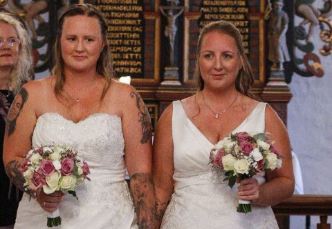 LYKKELIGE: Merethe Lie Nilsen (t.v.) og Anita Bengtson smiler fornøyde etter å ha blitt viet i Berg kirke. Brudeparet er de to første likekjønnede som gifter seg i en kirke i Halden.