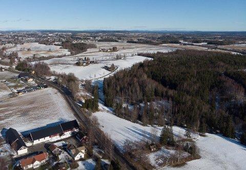 OVERSIKT: Området hvor det planlegges massedeponi er i ravinen øst for Trondheimsveien, som er veien til venstre i bildet.Næringsområdet er planlagt i det skogkledde området til høyre i bildet og deler av ravinen. I bunnen av ravinen renner bekken Jeksla. Bildet et tatt syd-nord. Øverst i bildet ser vi bebyggelsen på Kløfta.