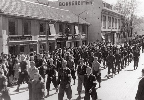 FRIGJØRINGEN: Hjemmestyrkene marsjerer gjennom Kongsberg sentrum etter frigjøringen.  19 personer fra Kongsberg falt forskjellige steder i verden under krigen. Nå skal navnene samles på et nytt minnesmerke.