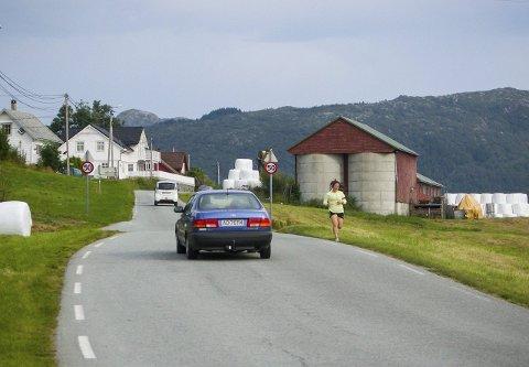 LITE PLASS: Denne bilen måtte ta ein tur over i motgåande felt for å ikkje komma for tett på denne kvinnelege joggaren. Hadde det komme bil i mot, hadde ikkje det vore mogleg. Plassen langs vegen er liten, trafikken er derimot stor. FOTO: YNGVE GAREN SVARDAL