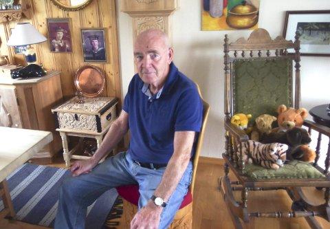 JUBILANT: Gerhart Larsen er en dyktig treskjærer og har laget både stolen han sitter på og klokka i bakgrunnen. Søndag fyller den tidligere skihopperen, turneren og ikke minst tistedølen 85 år. Foto: Tille Andreassen