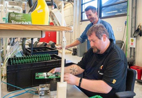 """LAGER """"HJERNEN"""": Jan-Arne Johansen (foran) og Klaus Hamar er to av mange ved Topro Elektonikk som er involvert i produksjon og salg av komponenter til en robot som tar knekken på både virus og bakterier."""