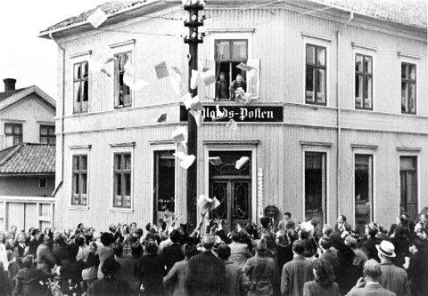 KASTET UT AVISER: Da freden kom 8.mai 1945 var det mange i Larvik som ikke hadde tid til å vente på at avisa skulle komme hjem i postkassa. Avisa ble derfor kastet ut av vinduet til folk under.