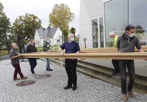 BLYTUNGT: Ut fra container og inn i kirken med en av de lange eikekonstruksjonene som skal monteres i fasaden på nytt orgel. Fire tyske teknikere har ankommet, er blitt koronatesta og starter jobb som foreløpig tar tre uker.