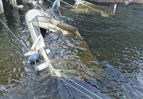 Gått under: Denne båten har ligget under vann ved industriområde i Knarrdalstrand i minst én uke. Nå har flere reagert, da man frykter at båten lekker drivstoff til elva. Brannvesenet melder at de har vært på stedet med lenser og gjort hva de kan. – Regninga blir sendt til eier, opplyser vakthavende brannsjef, Jon Erik Bergendahl. Foto: Privat
