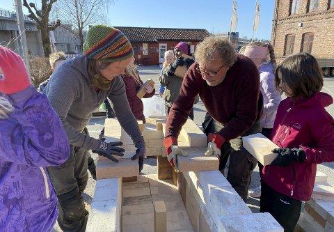 FYR OG FLAMME: Fjerdeklassingene fra Vestsiden skole hjalp ivrig til å bygge vedovnen som keramikken skal brennes i. Trine Midtsund og Ole Morten Kvam veiledet elevene gjennom prosessen.