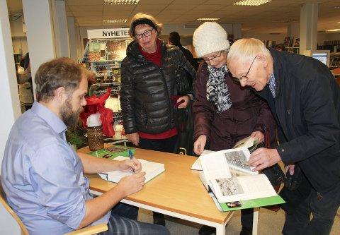 Signatur: Forfatter Håvard Havin Kongsrud signerte et eksemplar av boka for Unni Beate Bergsland. Mens Aud Andersen og Thor Andersen blar spent i den nye boka. Alle foto: Beate Sloreby
