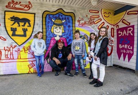 ELEVKUNST: Fire elever ved Alvimhaugen barneskole hadde laget tegninger som Are Buraas dekorerte en av veggene på skoleskuret med. Elevene var fornøyd med jobben Buraas hadde gjort. Fra venstre: Elsa Bugge Dahle, Are Buraas, Julian Kjennsjø, Blerta Rama og Bajrema Novalic. ALLE BILDER: JOHNNY HELGESEN