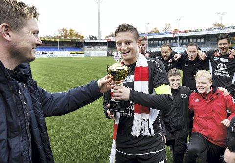 Rykket opp: Sunndal vant 4. divisjon i år. Her får kaptein Eivind Lervik pokal som synlig bevis på seriegull av Stig Arild Råket fra Nordmøre og Romsdal Fotballkrets.
