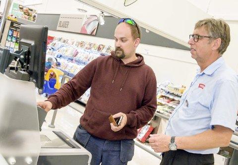 Butikksjef Odd Horntvedt på Meny Øya følger med når Jan Georg Lauvåsen kjøper dagligvarer i den selvbetjente kassa.