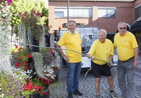 DUGNAD: Torbjørn Sletten (t.v), Terje Kristiansen og Odd Rummehoff er tre av eikværingene som jobber dugnad med å vanne blomsterprakten i Hokksund sentrum.