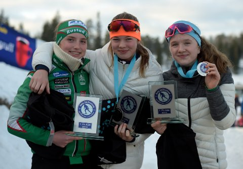 GULLJENTER: Rustads Karoline Longva og Ingeborg Roll Mosland og Mathea Perlestenbakken Barland strålte etter å ha motatt sine premier etter stafettseieren.
