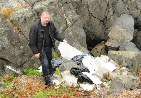OPPGITT: Miljøkonsulent i Nordkapp kommune, Alexander Eliassen, er oppgitt over at folk dumper søppel i naturen når det finnes tilgjengelig søppelfylling på Hammernes. Her har noen dumpet søppel ned mot sjøen ved E69. (Foto: Ellisiv Brattfjord )