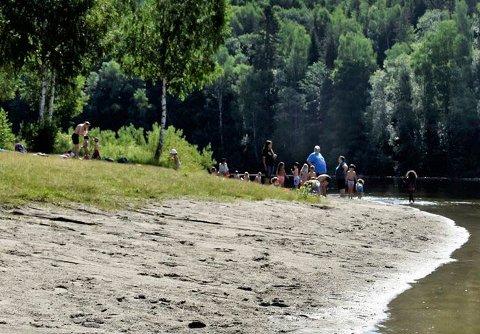 POPULÆR BADEPLASS: Bystranda i Schjongslunden blir mye brukt på finværsdager. Per-Erik Berge er skeptisk til at kommunen har anlagt en strand her. Bader Gro Helene Skalstad mener det går fint å bade, men at folk må være forsiktige og være nær land.