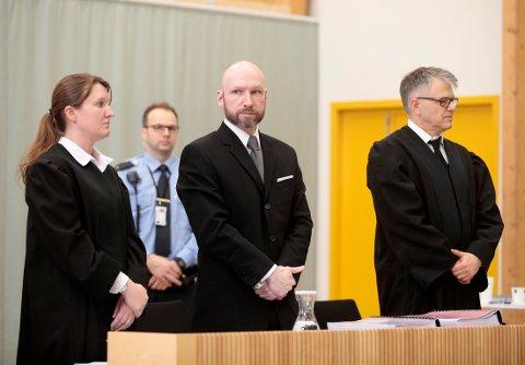 Anders Behring Breivik under behandlingen av søksmålet mot staten i 2017. Ved siden av ham står advokatene Mona Danielsen og Øystein Storrvik.