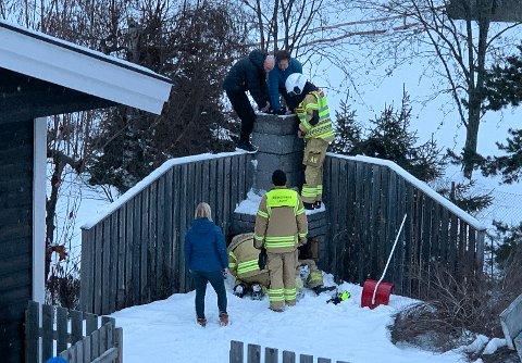 PIPEDRAMA: Fire brannmenn og to gode naboer hjelper mor til å få seksåringen opp igjen fra pipa.