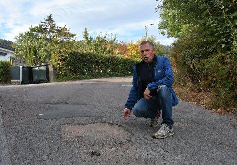 STORE HULL: Tor Karoliussen bor i enden av Tangenveien. For å komme til huset sitt må han kjøre over flere store hull i veien.