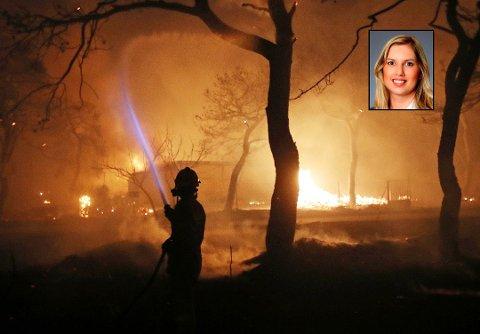 En gresk brannmann kjemper mot flammene i Mati, øst for Athen, mandag 23. juli. Foto: Thanassis Stavrakis, AP / Scanpix