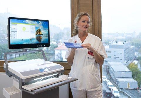 Sykepleier Henriette Gamlem demonstrerer en av de nye legemiddeltrallene som skal tas i bruk ved nye Haraldsplass diakonale sykehus.
