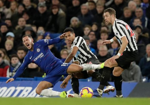 Chelsea's Eden Hazard, left, is tacked by Newcastle United's Isaac Hayden, center, during the English Premier League soccer match between Chelsea and Newcastle United at Stamford Bridge stadium in London, Saturday, Jan. 12, 2019. (AP Photo/Matt Dunham)