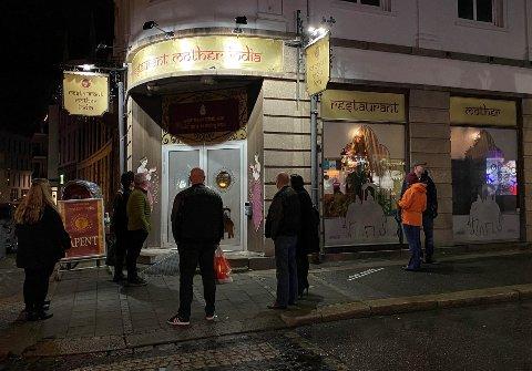 Ved 19.00-tiden sto folk i kø - med god avstand - inne i restauranten. Så mange var de at en rekke gjester også ble stående utenfor for å kunne holde god nok avstand.