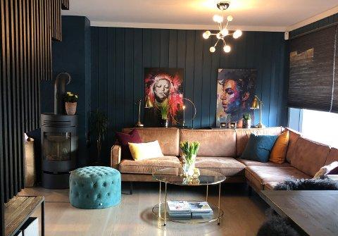 Blå vibber: Stua er malt i fargen Industrial blue. I hjørnet står en skinnsofa og gull gå igjen i detaljene. Foto: Privat