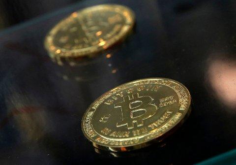 Symbolske bitcoin-mynter plassert på en tellemaskin i Hongkong. Foto: Kin Cheung / AP / NTB scanpix Foto: (NTB scanpix)