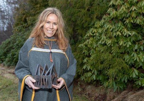 Utstiller: Christin Løkke er iført en tradisjonell samisk kappe som kalles Luhkka. I hånden har hun en utgave av naustet hun stiller ut i Bodø, men i noe mindre målestokk
