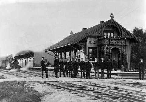 """Personalet på Hønefoss stasjon i 1896 med stasjonsbygningen og tog 184 """"Slaven"""" i bakgrunnen."""