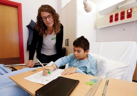 UNDERVISNING PÅ SENGEKANTEN: Lærer på somatisk avdeling Kari Troland har undervisning med 10 år gamle Chad André Escalante Larsson ved sykesengen på barnevdelingen på Haugesund sjukehus.