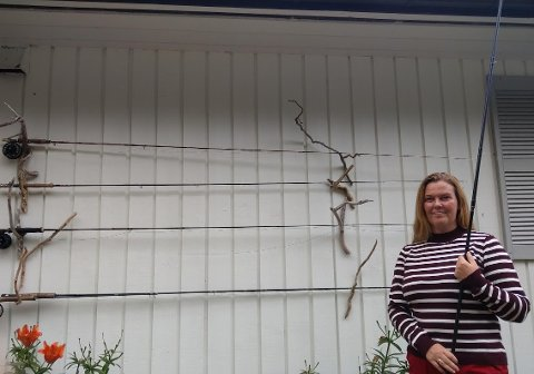 Marita Fjellstad Mårdalen med konkurransestanga. Den er tohånds og lengre enn vanlig. På veggen henger en rekke stenger som også er fluestenger.