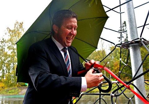 Ordfører Truls Wickholm måtte holde styr på både saks, bånd og paraply samtidig som han klippet snora til det nye klatretårnet ved Tangenten. Foto: Trond Folckersahm