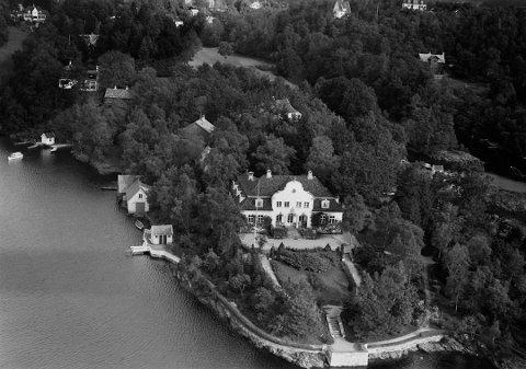 Dette flyfotoet frå 1930-talet viser korleis Ole Landmark såg for seg kjøpmann Edvard Riisøens landsstad. Det er i desse dagar hundre år siden anlegget blei bygd. Framleis held Riisøen-familien hus her, men no bur dei der heile året.