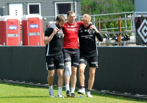 LEI SKADE: Igor Spiridonov måtte ha hjelp av naprapat Ole Martin Tunheim (t.v.) og keepertrener Thomas Romarheim Solberg etter å ha pådratt seg en skade på trening forrige fredag.