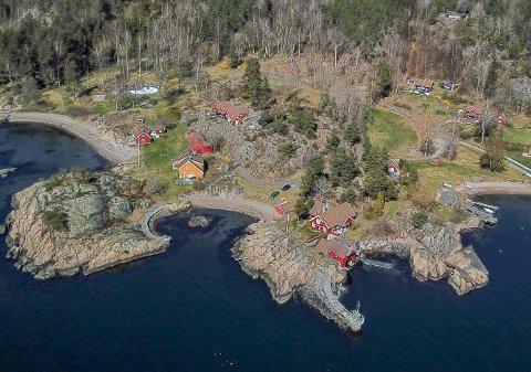 Eiendommen som er solgt består av det røde hovedhuset på knausen, gjestehuset til venstre og tennisbanen bak til høyre.