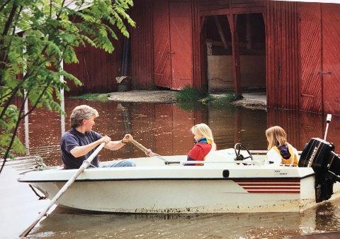 ROR PÅ GÅRDEN: Marte Holmboe Berg (bakerst i båten) blir rodd rundt på gården av pappa Per Edvard Berg for å se på skadene etter flommen 2. juni 1995. Dette bildet er tatt to dager etter flomtoppen. Veslesøster Maren i midten.