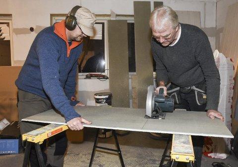 Skytterpappa Jørn Ove Sandstad gir Gunnar Laukholmen hjelpende hånd i kutting av en sponplate.