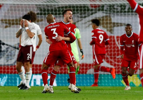 Liverpool's Diogo Jota, centre, is congratulated by teammate Fabinho after scoring his team's third goal during the English Premier League soccer match between Liverpool and Arsenal at Anfield in Liverpool, England, Monday, Sept. 28, 2020. (Jason Cairnduff/Pool via AP)
