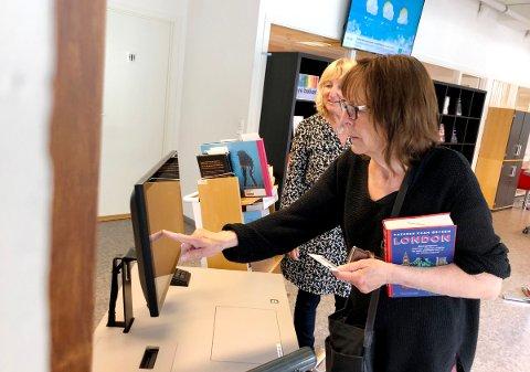 SELVBETJENING: Mona Vegdal bruker selvbetjeningsautomaten for å registrere utlånet. I bakgrunnen fagleder Britt Døvle Larssen.
