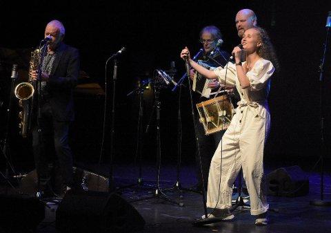 ROCKET: Trondheimeren Karianna Sommerro framførte Jørgens Gravvolds Bøverdalsrock med stil. Med foreldre fra Surnadal og Halsa kan hun surnadalsdialekten utmerket, og knotet ikke på en lyd underveis på den fengende melodien som hennes pappa Henning Sommero (bak) har laget. John Pål Inderberg (til venstre) og trommis Jo Inge Nes bidro også med sitt.