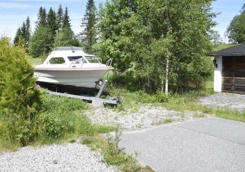 Hensatt: Noen har tatt seg til rette og plassert båt, med motor og på henger, i enden av Løkkaveien på Flateby. I vinter ble derfor snø måkt inn foran garasjen til høyre. Naboene håper noen kan fjerne båten.