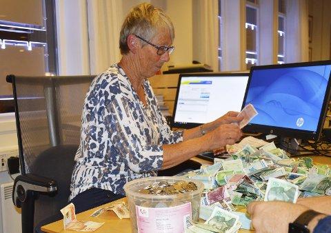 PENGETELLING: Anne Berit Holden telte penger samlet inn i bøsser. Flere frivillige brukte tid på det søndag kveld.
