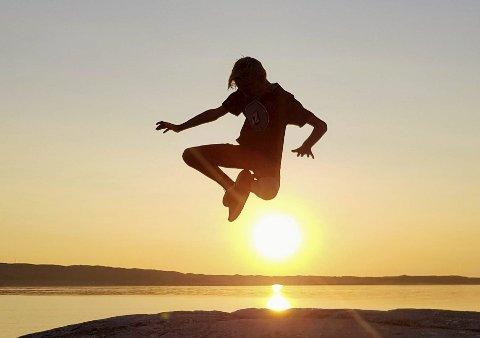 SPRELSK SOLNEDGANG: Ukevinneren har fanget Sigurd som spretter høyt i solnedgangen på Kalvhyllodden. Juryen mener vinneren har planlagt dette godt, men har også truffet godt. Solnedganger som utnyttes liker juryen.Foto: Anne Marte Almås
