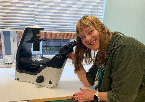 TILBAKE PÅ PLASS: Mette Serine Wesmajervi Breiland i laben med det samme mikroskopet som måtte brukes på kreativt sett da koronaviruset herjet som verst.