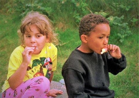 Vennskap. To gode venner spiser is. Jente og gutt. Svart og hvit. Begge er norske barn, med røtter fra to kulturer. Is, sommerferie. Jenta med Pokemon T-skjorte. Flerkulturell.   Foto: Berit Keilen / NTB scanpix